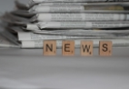 "Image of newspapers and scrabble tiles spelling ""news"""